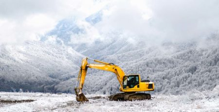 Yellow excavator in the snow